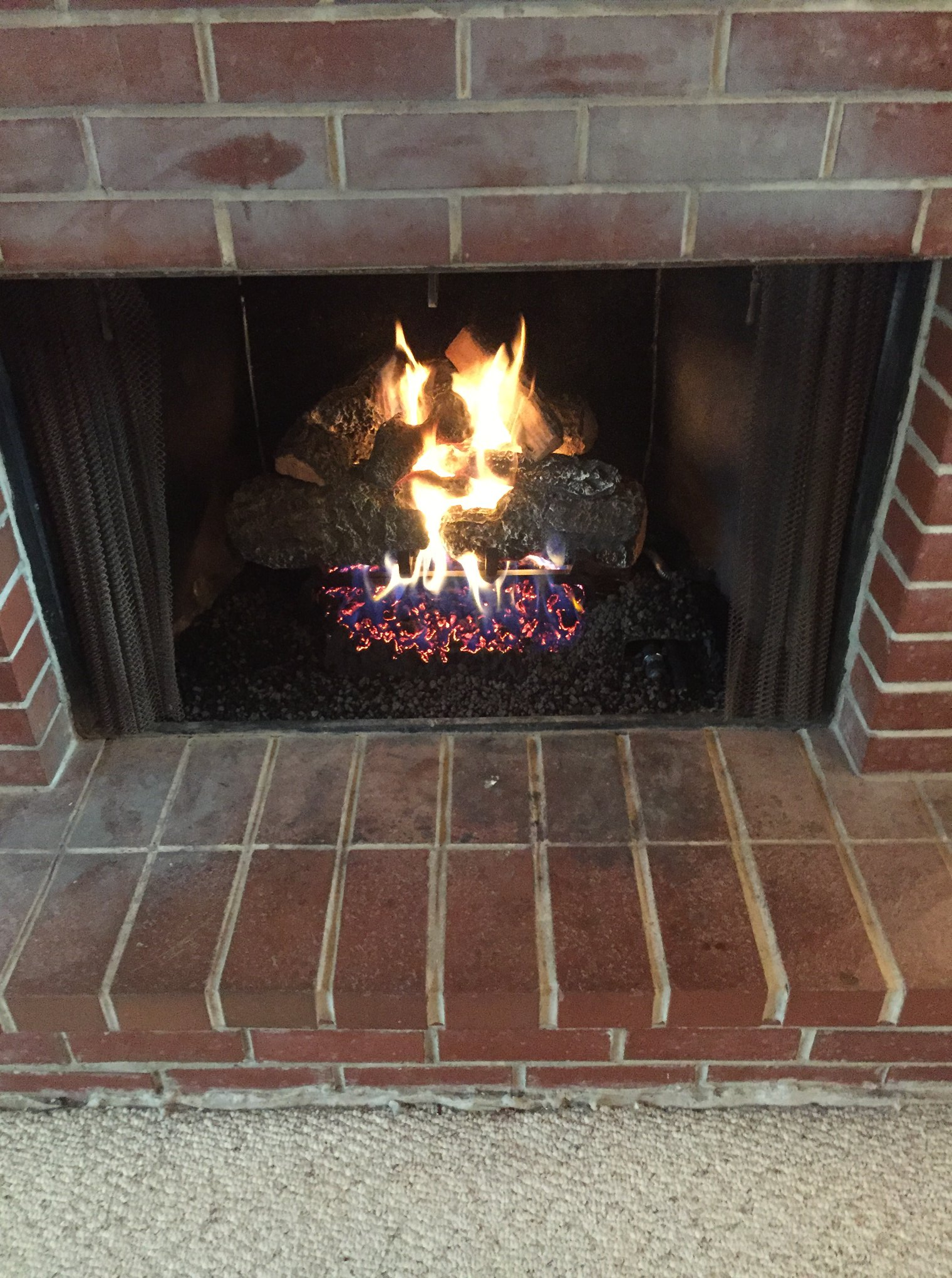 Hargrove radiant heat Cross Timber gas logs inside wood burning fireplace.