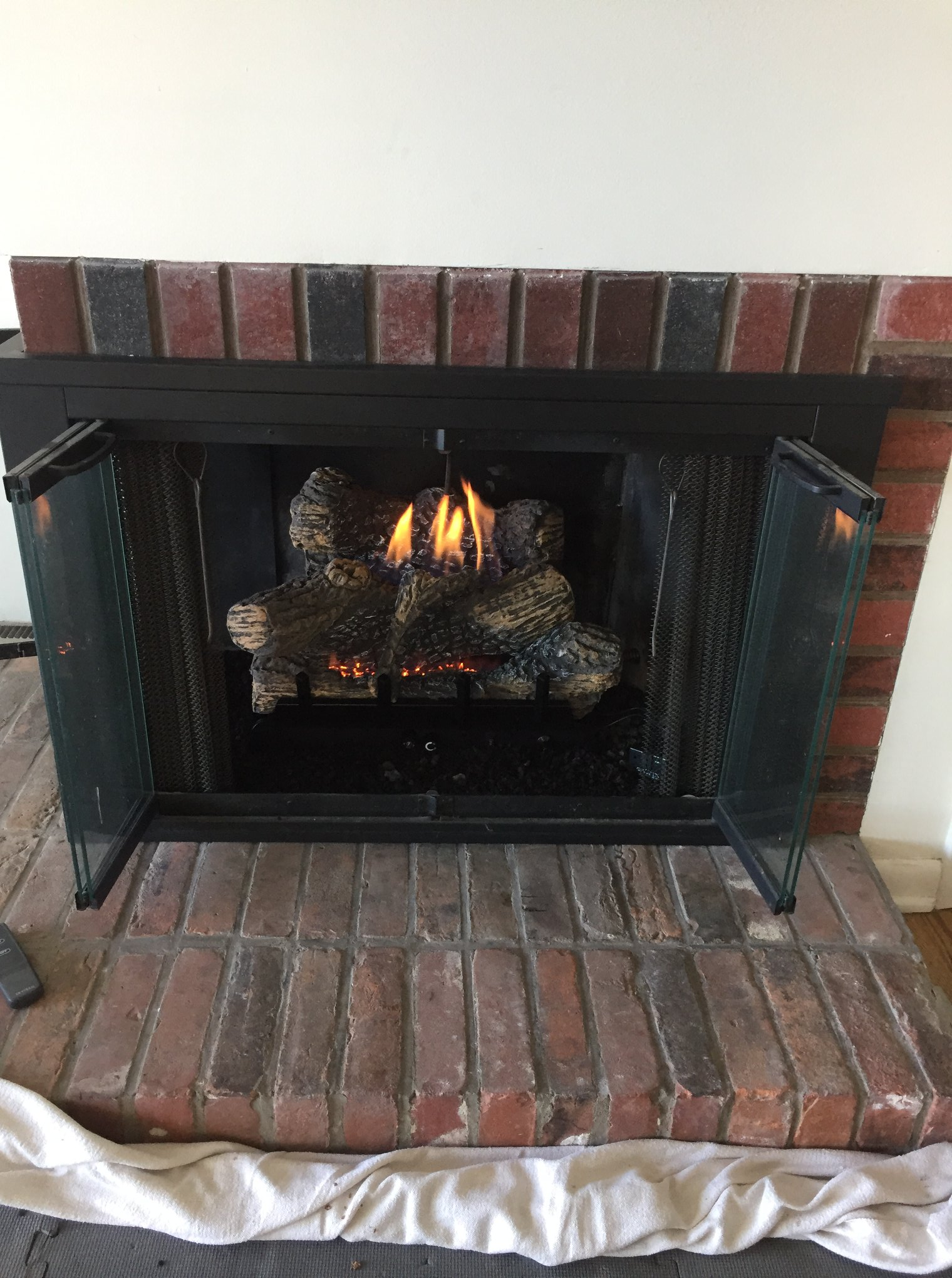 Recently installed natural gas log set into wood burning fireplace.